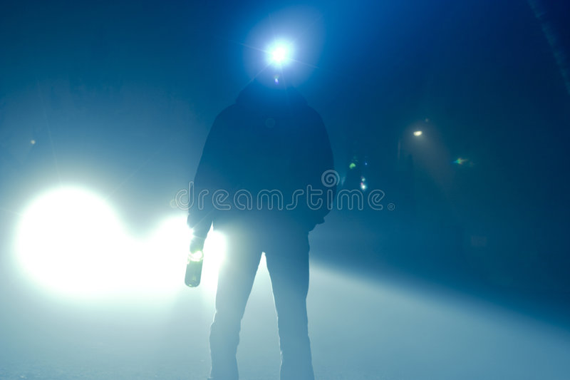 Searching Man. Car lights. silhouette of a man with a wine bottle in one hand and a search light on his head