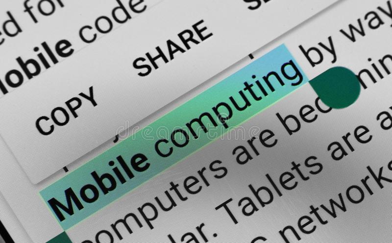 Word `Mobile computing` selected and highlighted digitally on mobile display screen royalty free stock photo