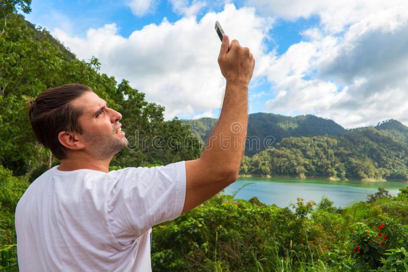 Searching for mobile connection in wild nature on vacation. Perfect day outdoor. Man with smartphone. Forest and lake landscape. Man making mobile photo. No stock images