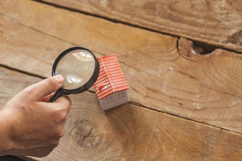 Searching a new home, real estate concept. Man looking to miniature toy house through a magnifying glass, Buy or sell the property royalty free stock photography