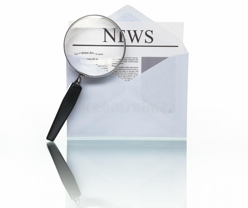 Searching for news. PHOTOGRAPH (NOT illustration or 3D render) of opened envelope mail and news paper with magnifying glass to symbolize searching for news, shot stock images
