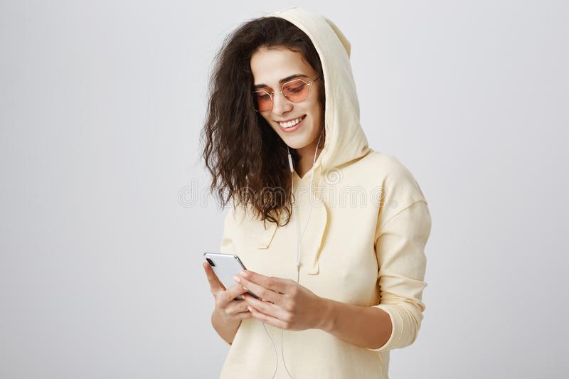Searching for right track to match her lifestyle. Portrait of positive joyful woman in hood and trendy sunglasses royalty free stock photos