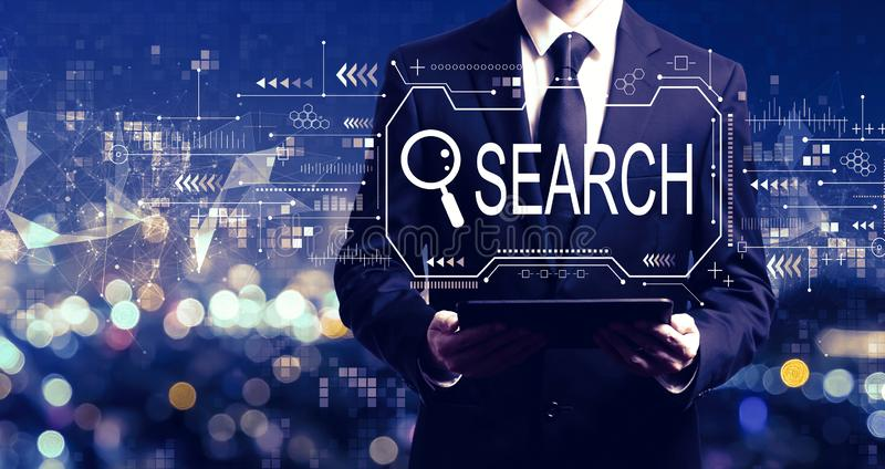 Searching theme with businessman holding a tablet royalty free stock photography