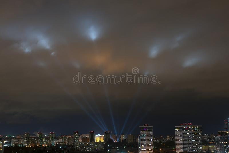 Searchlights shine in the night sky over the city royalty free stock photography