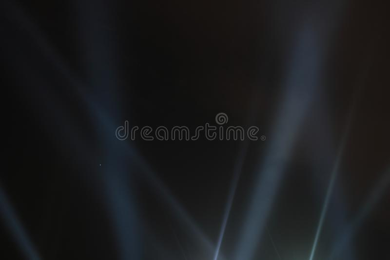 Searchlights shining beams of light into the black sky. Abstract background. Searchlights shining beams of light into the black sky stock photography