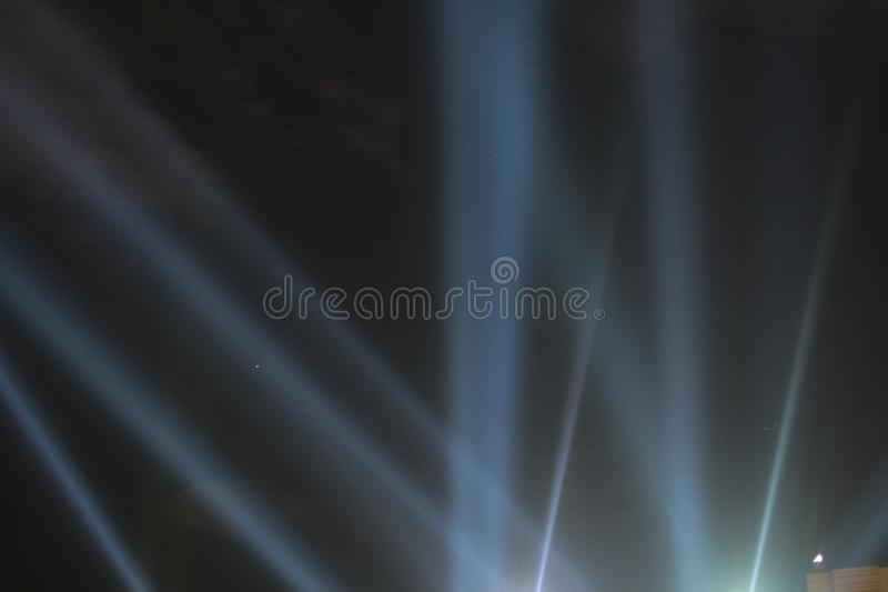 Searchlights shining beams of light into the black sky. Abstract background. Searchlights shining beams of light into the black sky stock photo