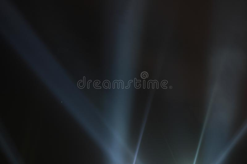 Searchlights shining beams of light into the black sky. Abstract background. Searchlights shining beams of light into the black sky stock image