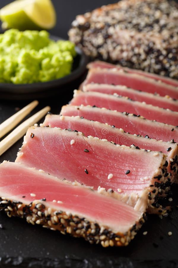 Seared ahi tuna coated sesame seeds with wasabi macro. Vertical royalty free stock photo