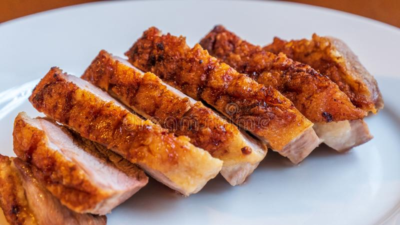 Seared duck breast with crispy skin on a white ceramic plate stock photo