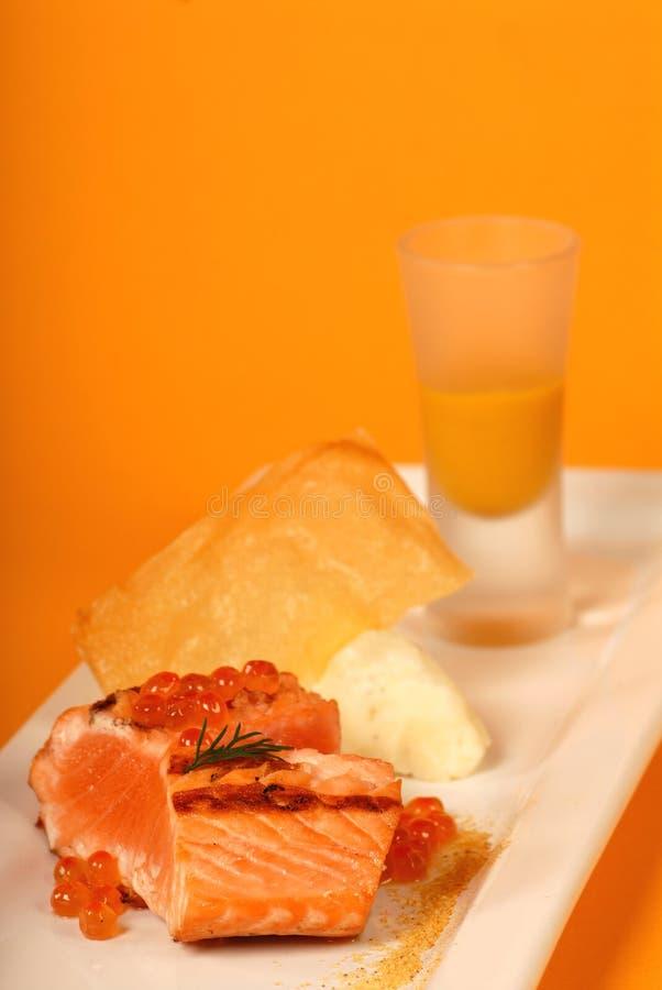 Seared salmon with caviar and pumpkin soup stock photos