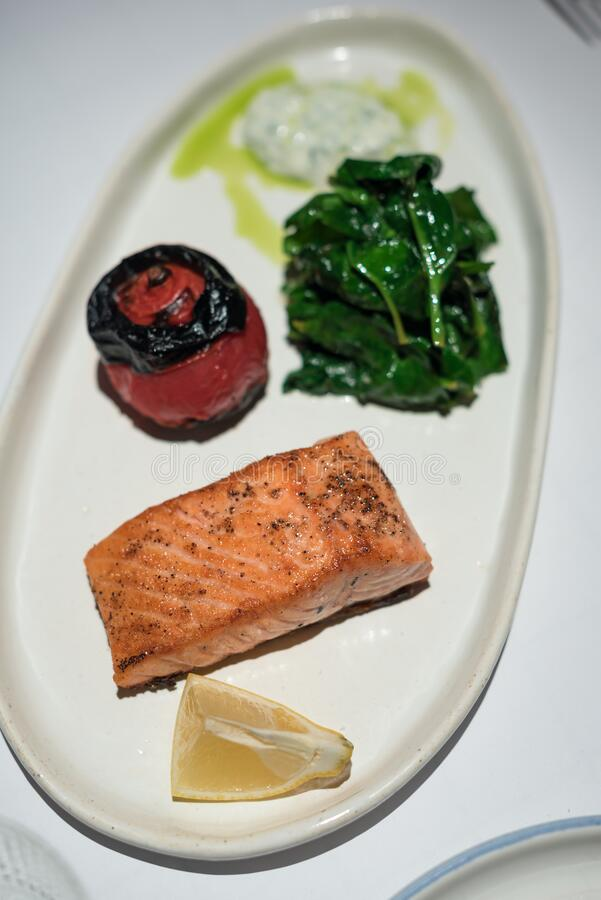 Seared Salmon Served with Roasted Tomato and Wilted Spinach. Healthy Lunch royalty free stock photos