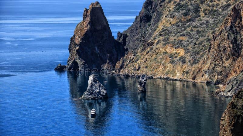 Seascape βουνά και βράχοι ένα μόνο σκάφος στο νερό στοκ φωτογραφίες με δικαίωμα ελεύθερης χρήσης