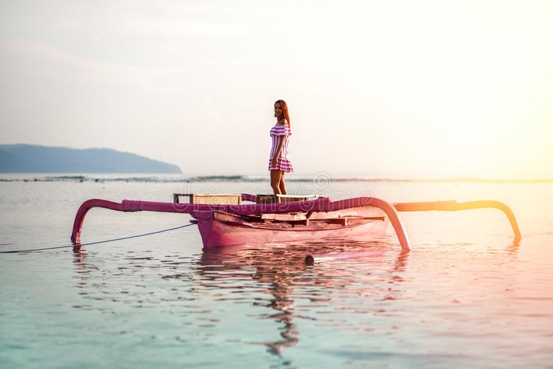 Seascape με ένα νέο κορίτσι και μια ρόδινη βάρκα στο κέντρο στο ηλιοβασίλεμα στο νησί Gili Ινδονησία στοκ εικόνες