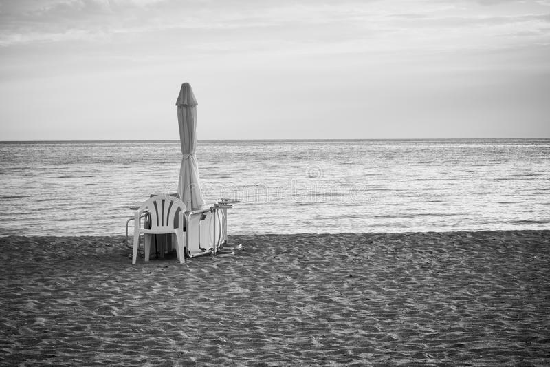 Seascape πρωινού, μοναξιά, εξαρτήματα παραλιών - ομπρέλα, αργόσχολος και καρέκλα στην αμμώδη παραλία στοκ φωτογραφίες