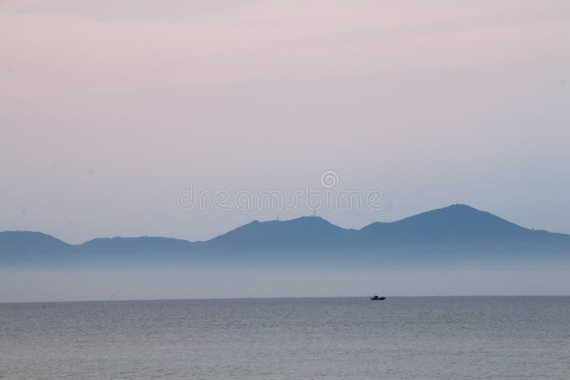 Seascape σούρουπου της Misty με τους λόφους τον ορίζοντας στην παραλία dai cua, Β στοκ φωτογραφία
