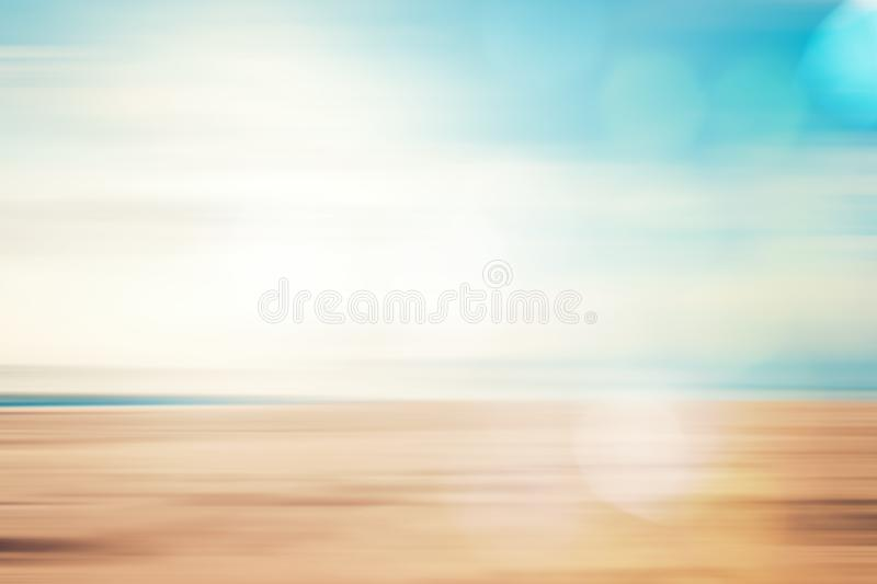 A seascape abstract beach background. Panning motion blur and bokeh light of lens flare, pastel colors in a vintage and retro style royalty free stock photography
