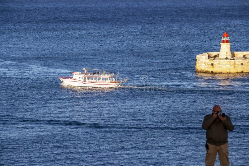 Seascape azul profundo com o farol do quebra-mar de Ricasoli e um navio de cruzeiros no porto grande, Valletta, Malta foto de stock royalty free