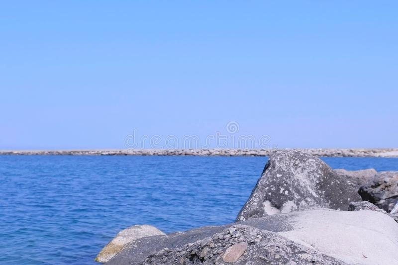 Background seascape with sea stone beach and pier in bay at sunny day. stock images