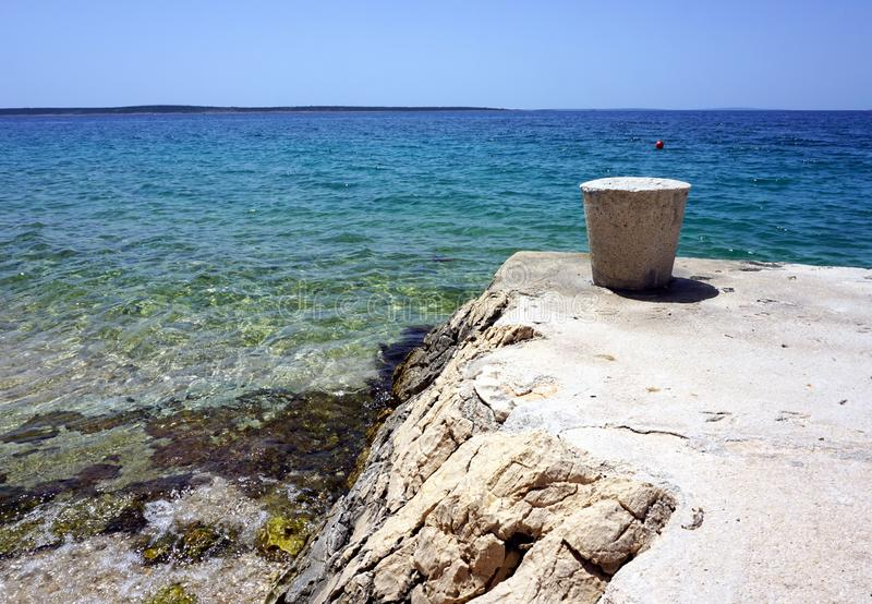 Stone mooring bollard on the beautiful seashore with clear blue sea water in the background royalty free stock photo