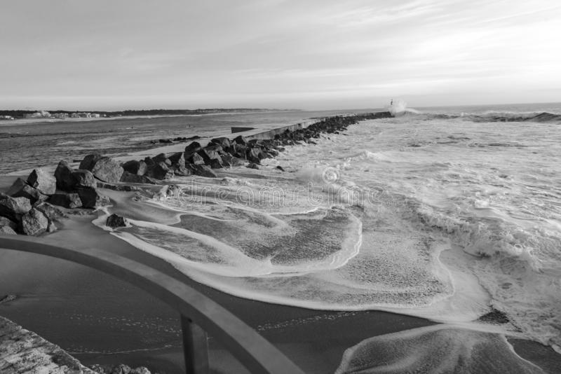 Seascape the bay and the lighthouse Vila do Conde. Black and white seascape of ocean waves in the bay of Vila do Conde Farol the Azurara royalty free stock photos