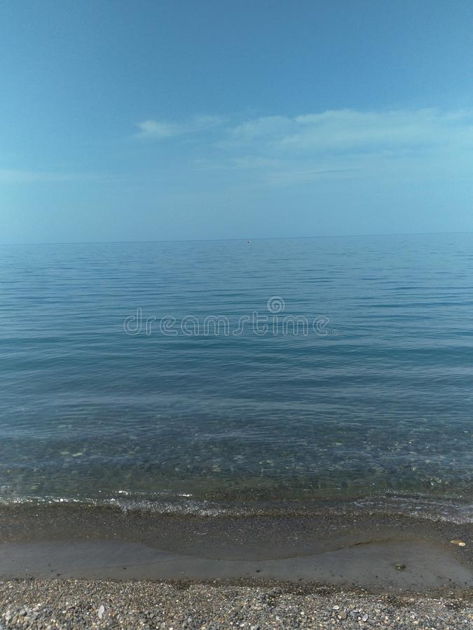Seascape in blue tones, the horizon line is located in the center of the image, there is free space for text, copy space, vertical. Seascape in blue tones, the royalty free stock photos