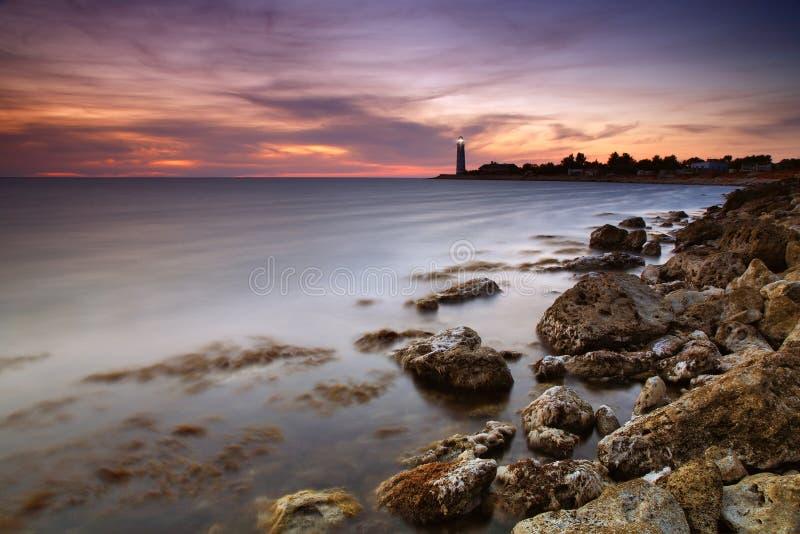 Seascape bonito com um farol no por do sol imagem de stock