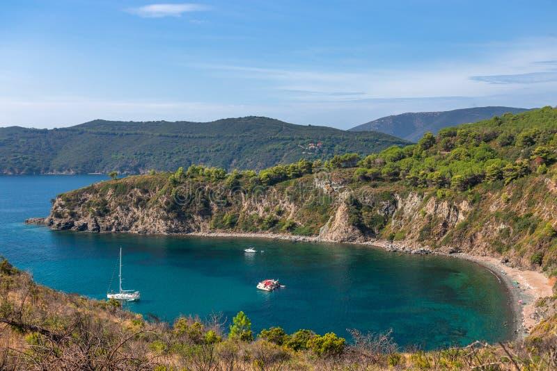 Seascape bonito em uma praia selvagem pequena de Elba Island na lagoa esmeralda do mar com barco de navigação Toscânia, Italy foto de stock royalty free