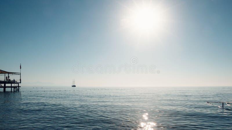Seascape bonito Opinião de Minimalistic do mar e do navio de navigação no amanhecer Navigação no mar na luz solar da manhã foto de stock