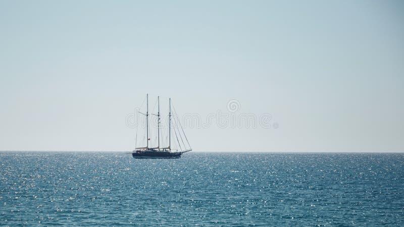 Seascape bonito Opinião de Minimalistic do mar e do navio de navigação no amanhecer Navigação no mar na luz solar da manhã imagem de stock