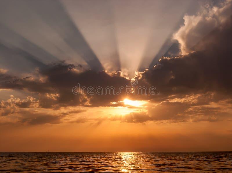 Seascape cênico bonito do por do sol com o sol que olha para fora atrás da nuvem que gera irradiando raios de sol e refletindo da imagens de stock