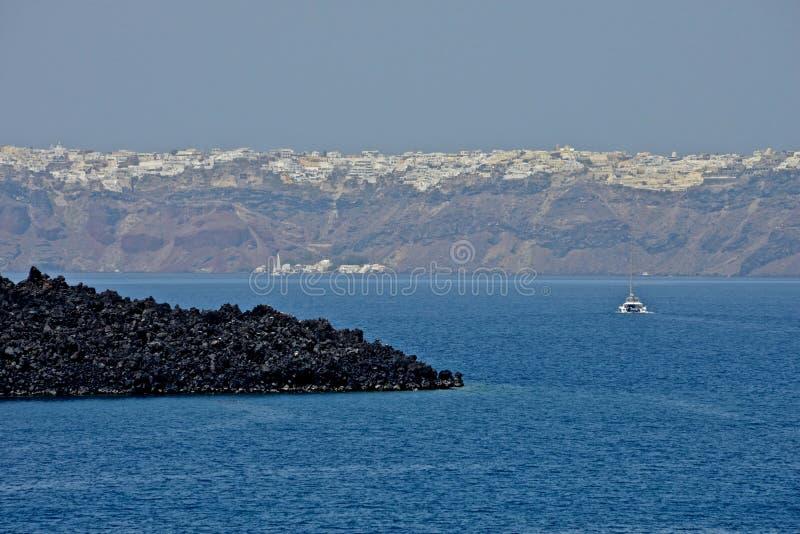Seascape Caldera του νησιού και του νησιού Santorini με μια πλέοντας βάρκα στοκ φωτογραφία