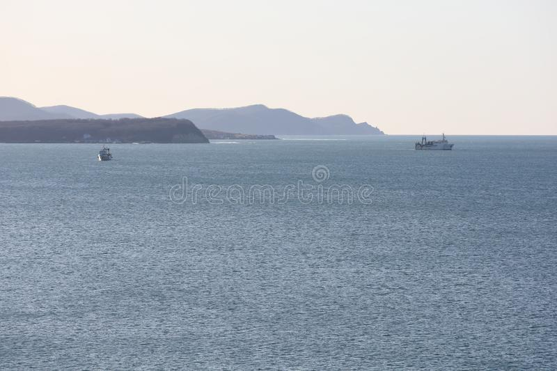 Seascape with capes, mountains and fishing vessels at anchor. Marine bay, good weather. Seascape with capes, mountains and fishing vessels at anchor. Marine bay royalty free stock images