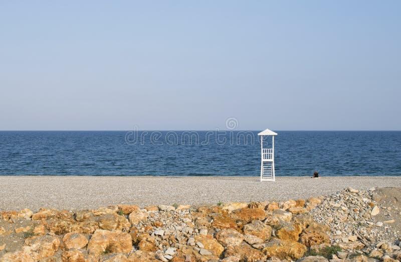 Seascape com a cabana da salva-vidas no fundo calmo do céu Praia com homem só imagem de stock