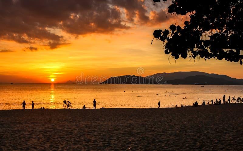 Seascape com nuvens coloridas, o céu alaranjado e o The Sun no nascer do sol em Nha Trang