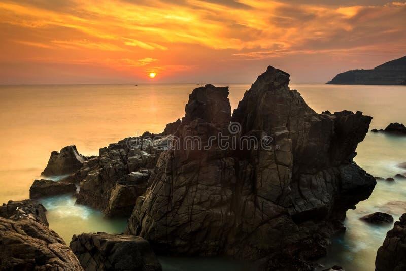 Seascape com pedregulhos exóticos, água de seda da natureza no nascer do sol alaranjado lindo fotografia de stock royalty free