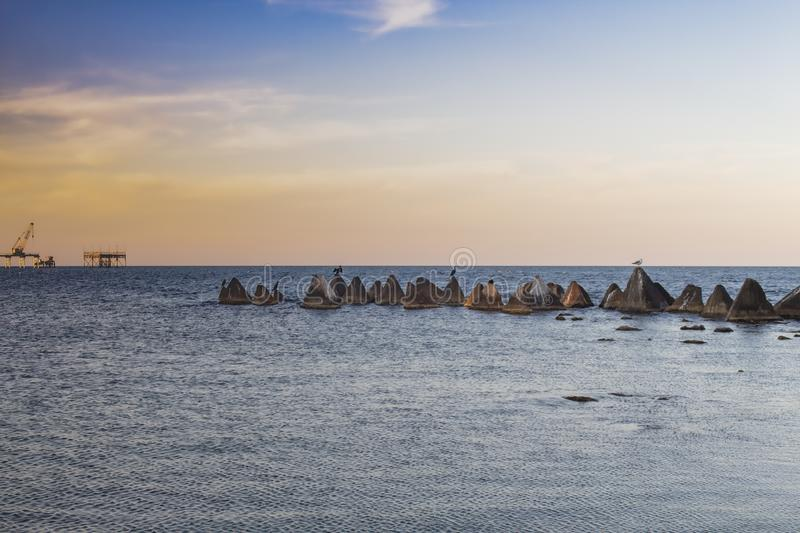 Seascape. Concrete pyramids with cormorants and gulls before sunset. Metal structures and a crane can be seen in the distance. Shabla municipality is the most royalty free stock images