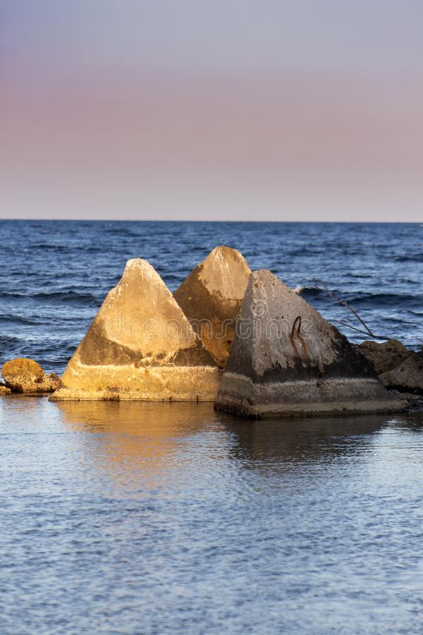 Seascape. Concrete pyramids in the light before sunset. royalty free stock photos