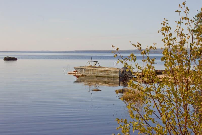 Seascape da manhã com um barco velho e umas passagens de madeira imagens de stock