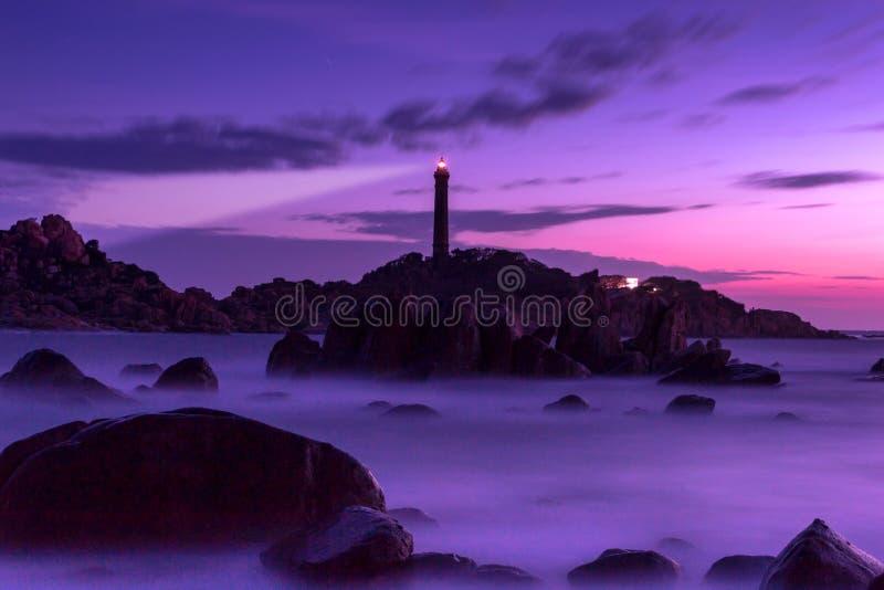 Seascape da natureza com rochas, as ondas borradas e a luz do farol após o por do sol imagem de stock
