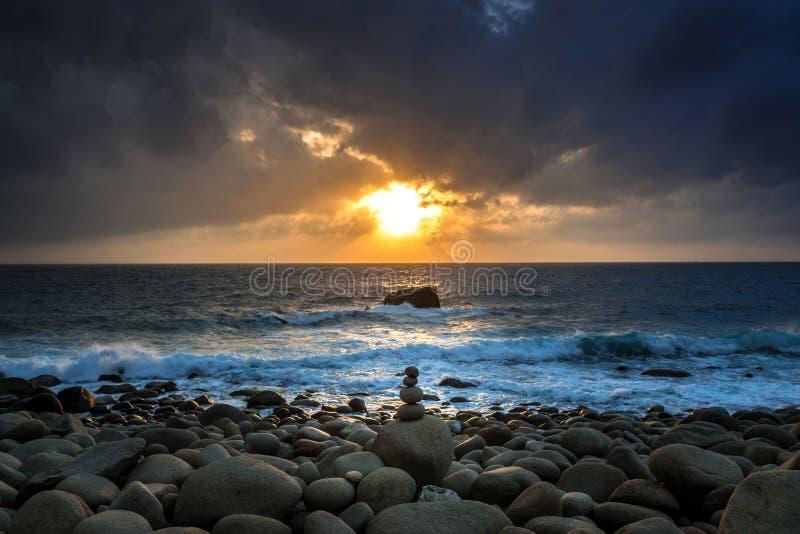 Seascape da natureza com Zen Stacked Rocks na praia em pouca luz do sol no alvorecer fotografia de stock
