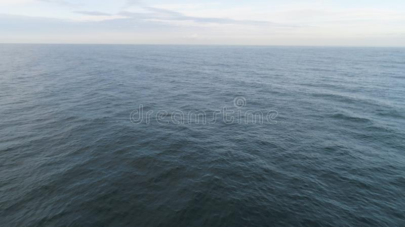 Seascape with dark blue sea with small waves, horizon, and cloudy sky. Shot. Aerial for calm sea or ocean with ripples stock image