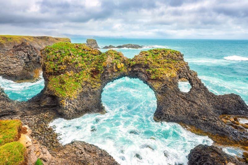 Seascape de surpresa, arco no penhasco vulcânico, costa atlântica da rocha do basalto, Islândia, fundo do curso fotos de stock royalty free