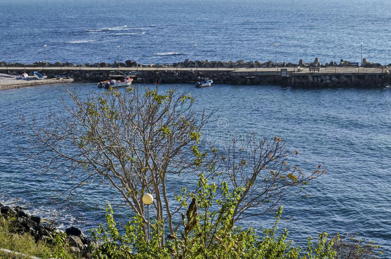 Seascape do cais para o barco de pesca com a estrada litoral no Mar Negro e a praia pequena perto da cidade antiga Nessebar fotografia de stock royalty free