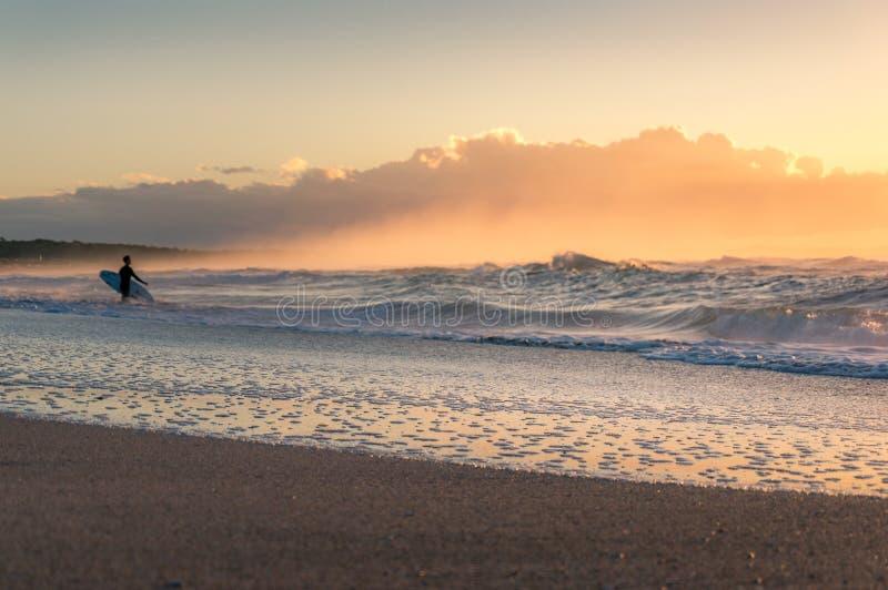 Seascape do nascer do sol da praia com o surfista na distância Fundo do ver?o do beira-mar fotografia de stock royalty free