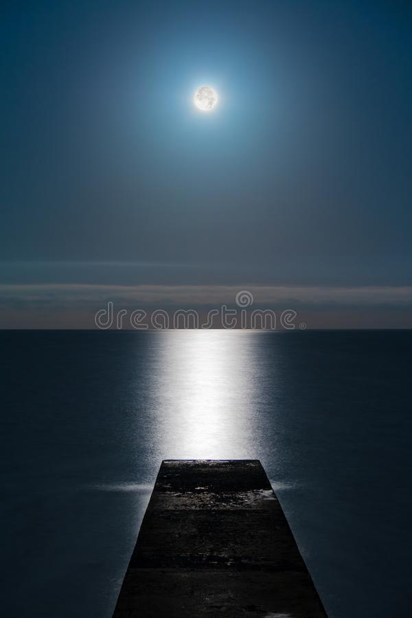 Full moon over sea. Seascape with the full moon over the sea and the mole in line with the moon glade stock images