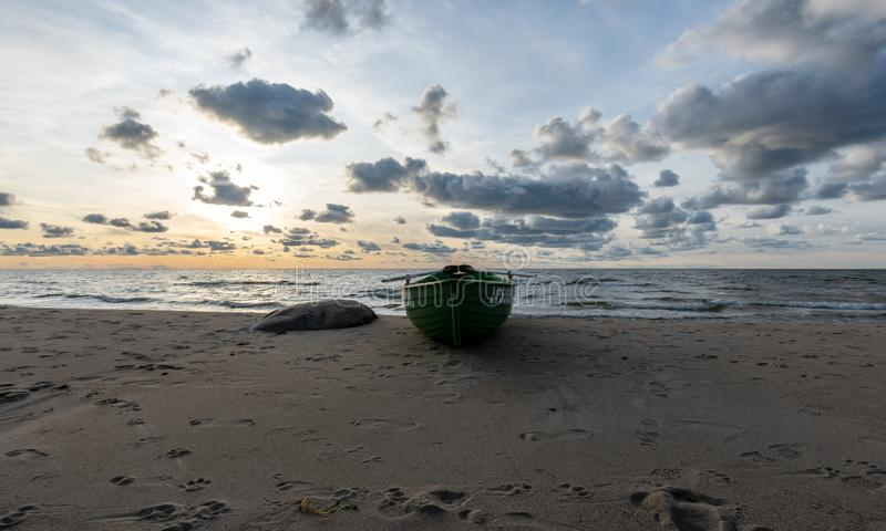Seascape image of the sea with cloudy sky before sunset,  stones and  of light before sunset, beautiful sunny day and quiet sea. Seascape image of the sea with stock photography