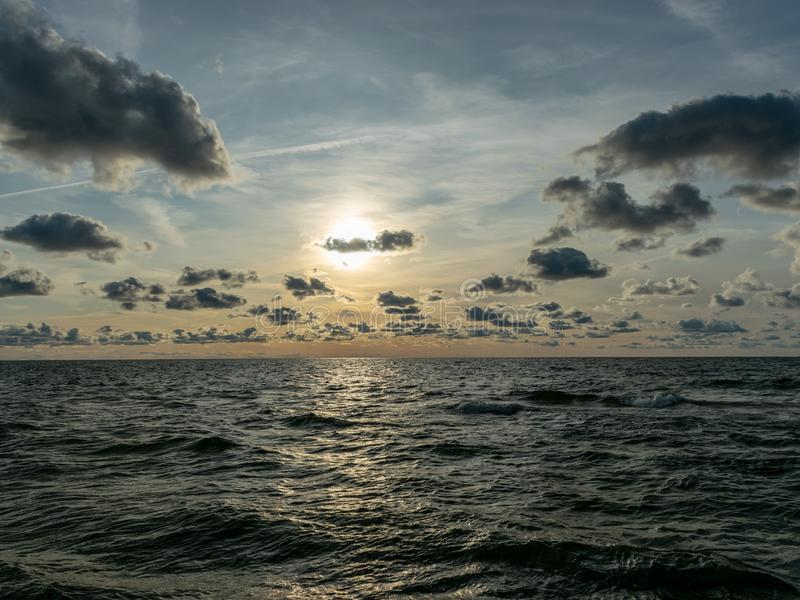 Seascape image of the sea with cloudy sky before sunset,  stones and  of light before sunset, beautiful sunny day and quiet sea. Seascape image of the sea with stock image