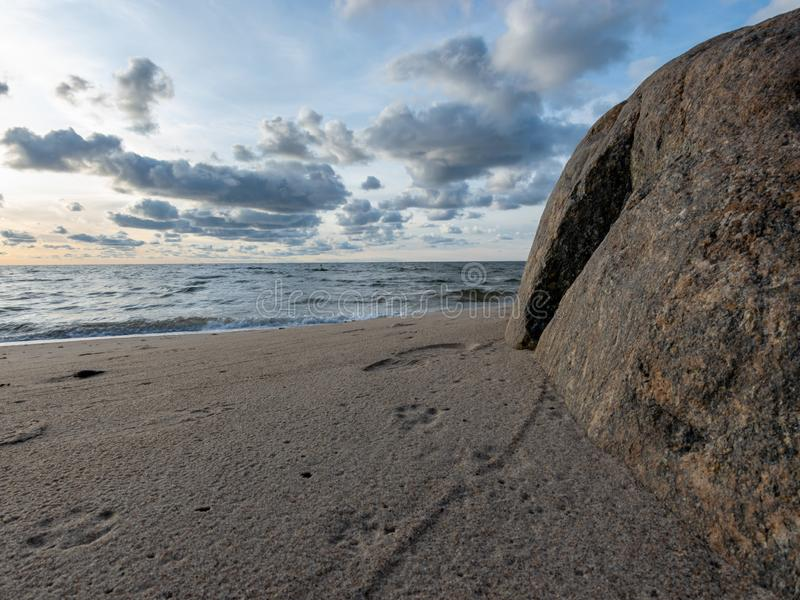 Seascape image of the sea with cloudy sky before sunset,  stones and  of light before sunset, beautiful sunny day and quiet sea. Seascape image of the sea with royalty free stock photography