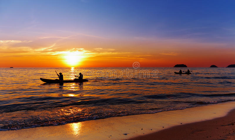 Seascape with kayakers at sunset royalty free stock image