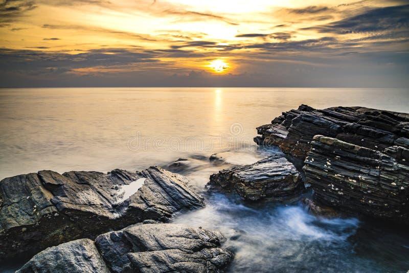 Seascape lång exponering av slågna havsvågor vaggar på kusten av Rayong, Thailand royaltyfria foton